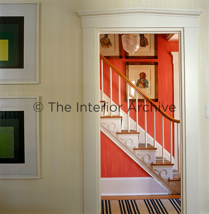 Antique prints of Native Americans line the watermelon colour walls in the entrance hall