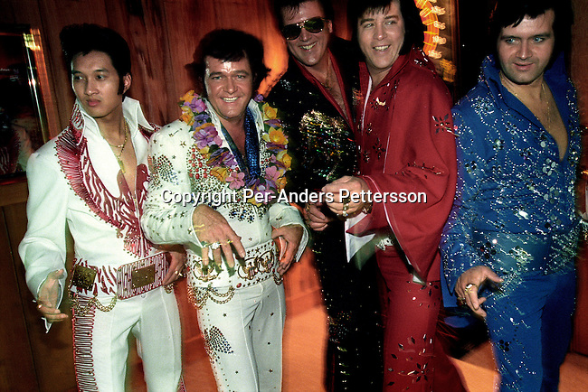 Unidentified Elvis Presley impersonators line up for a photo session on August 13, 1998 in Memphis, TN, USA. Elvis Presley died in August 1977 and every year thousands of people come to celebrate his memory during 2 weeks in Memphis. Impersonator contests are held in several places and the contestants come from all over the world. (Photo by: Per-Anders Pettersson)
