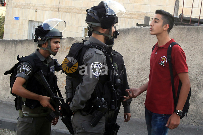 Israeli border guard block a Palestinian school boy from entering a road at a newly erected checkpoint in Jerusalem's neighborhood of Jabal al-Mokaber on October 19, 2015. Israeli police began erecting a wall in east Jerusalem to protect a Jewish neighbourhood subject to firebomb and stone attacks launched from an adjacent Palestinian village. Photo by Mahfouz Abu Turk