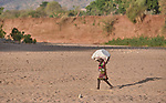 A girl carries things on her head in Gidel, a village in the Nuba Mountains of Sudan.
