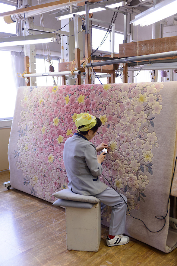 Riuko Moriya works on the shearing (3D relief) process of making a carpet. Oriental Carpet Mills, Yamanobe-machi, Yamagata, Japan, April 12, 2016. Oriental Carpet Mills was founded in 1935 and produces luxury hand-woven and tufted carpets. Its carpets are used all over the world, including in the Vatican, the Imperial Palace in Tokyo and the Kabukiza Kabuki Theatre.