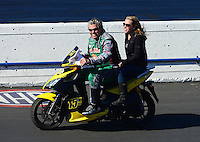 Nov. 10, 2012; Pomona, CA, USA: NHRA funny car driver John Force and daughter Brittany Force riding a scooter during qualifying for the Auto Club Finals at at Auto Club Raceway at Pomona. Mandatory Credit: Mark J. Rebilas-