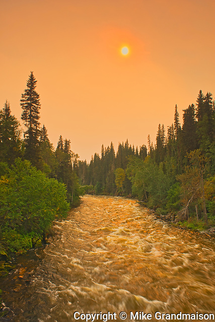 The Grass River and late afternoon sun with fire smoke in the air<br />