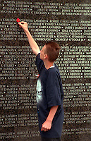 Boy 15 honoring a soldier at Vietnam Wall on Memorial Day. St Paul Minnesota USA