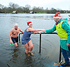 Serpentine Swimming Club <br /> Christmas Day Swimming race <br /> Serpentine, Hyde Park, London, Great Britain <br /> 25th December 2016 <br /> <br /> <br /> Robin helps a swimmer out of the Serpentine after the race <br /> <br /> Photograph by Elliott Franks <br /> Image licensed to Elliott Franks Photography Services