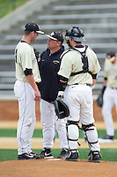 Wake Forest Demon Deacons assistant coach Dennis Healy (center) has a chat on the mound with starting pitcher Connor Kaden (40) and catcher Ben Breazeale (9) during the game against the Virginia Cavaliers at Wake Forest Baseball Park on May 17, 2014 in Winston-Salem, North Carolina.  The Demon Deacons defeated the Cavaliers 4-3.  (Brian Westerholt/Four Seam Images)