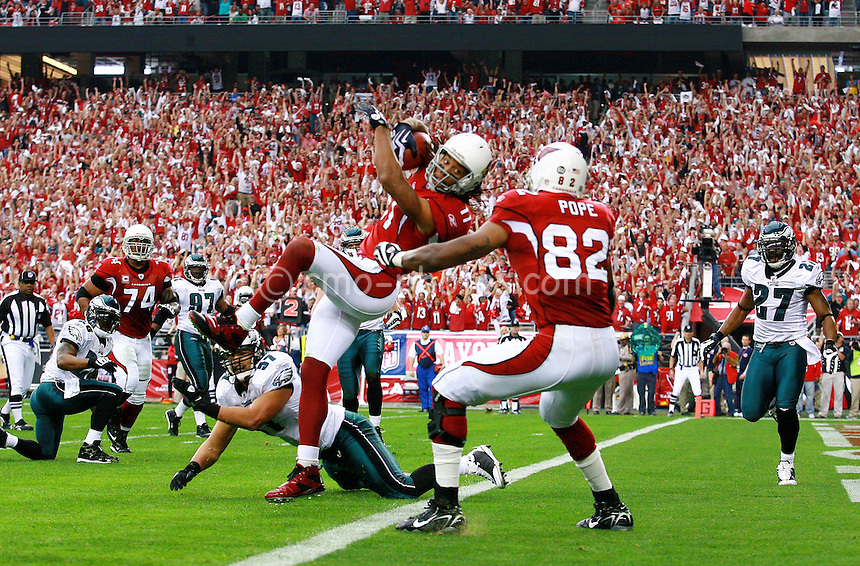 Jan. 18, 2009; Glendale, AZ, USA; Arizona Cardinals wide receiver Larry Fitzgerald (11) scores a touchdown against the Philadelphia Eagles during the first quarter of the NFC Championship game at University of Phoenix Stadium.