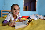 "THIS PHOTO IS AVAILABLE AS A PRINT OR FOR PERSONAL USE. CLICK ON ""ADD TO CART"" TO SEE PRICING OPTIONS.   Sarah Ismili, an 11-year old Roma girl in Suto Orizari, the Macedonian municipality that is Europe's largest Roma settlement, reads her school homework in her family's home."