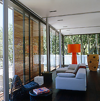 A sliding wooden screen shields the contemporary living room which is filled with modern furniture