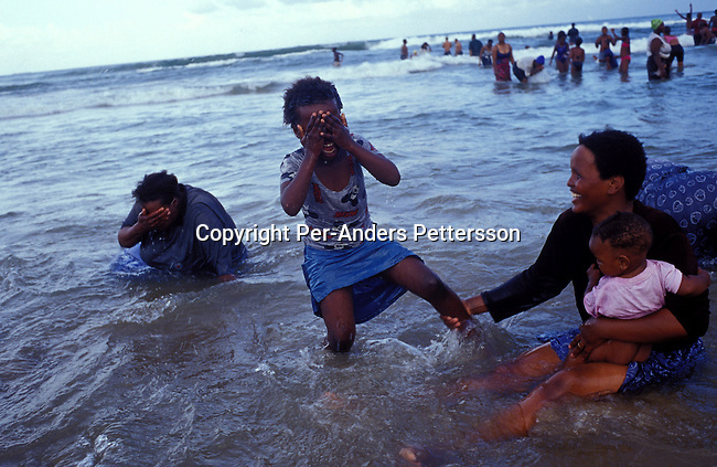 dipplei00085 .People Leisure DURBAN, SOUTH AFRICA - An unidentified family enjoys the sea as the sun sets on January 1, 2004 in Durban, South Africa. Durban is a popular tourist destination along the Indian Ocean and local people enjoy the beach on the weekends. The city has a big portion of Indian people..©Per-Anders Pettersson/ iAfrika Photos