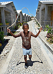 "Cheslin Basin, 8, jumps rope amid houses in a model resettlement village constructed by the Lutheran World Federation in Gressier, Haiti. The settlement houses 150 families who were left homeless by the 2010 earthquake, and represents an intentional effort to ""build back better,"" creating a sustainable and democratic community."