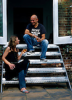 Owners Amanda Sellers and Martin Barrell relax with a glass of wine on the metal steps leading down to the patio