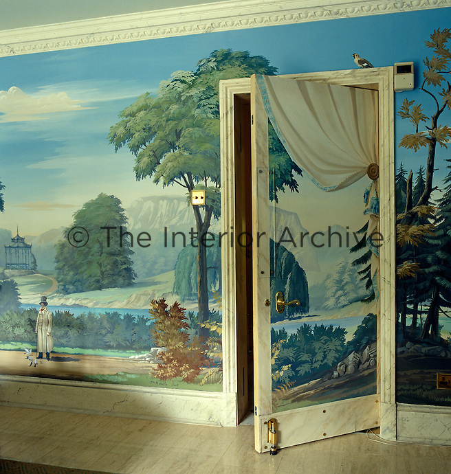 Trompe l'oeil drapery by Pierre-Marie Rudelle is painted on the back of the open door to the dining room with a bird perched on the door frame