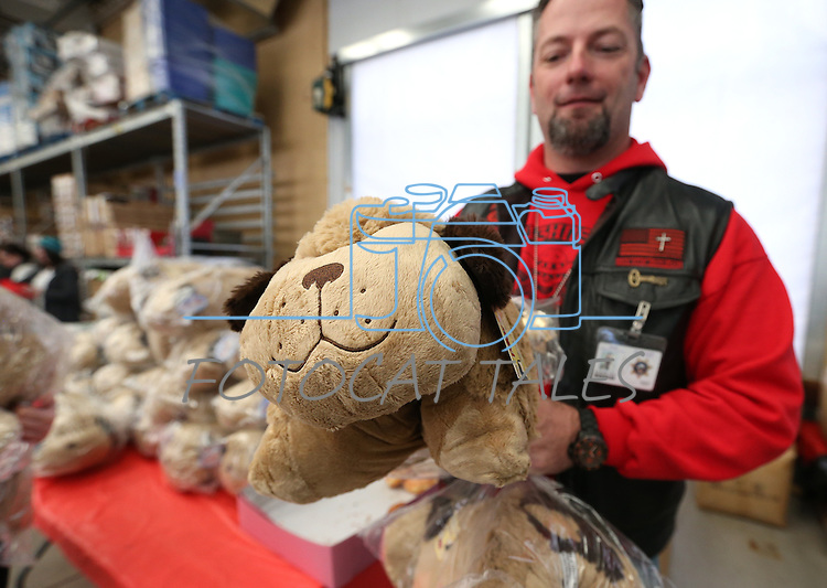 Paul Kluever, with the Roughnecks motorcycle club, hands out Pillow Pets at the 10th annual Holiday with a Hero event at Walmart in Carson City, Nev., on Wednesday, Dec. 17, 2014. The event pairs 200 of Carson City's K-5th grade homeless students with a local heroes for Christmas shopping. <br /> Photo by Cathleen Allison