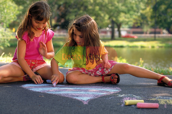 young girls creating art on sidewalk in park