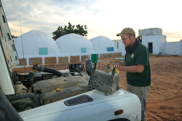 Africa, Mauritania, Sahara Desert, Chinguetti. A german traveller servicing his Land Rover Defender TD5 Station Wagon. --- No releases available. Automotive trademarks are the property of the trademark holder, authorization may be needed for some uses.