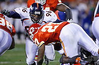 Denver Broncos tackle Michael Myers assists linebacker Al Wilson on a tackle to hold Chiefs running back Larry Johnson to a three yard gain on a run up the middle during the second quarter at Arrowhead Stadium in Kansas City, Missouri on November 23, 2006. The Chiefs won 19-10.