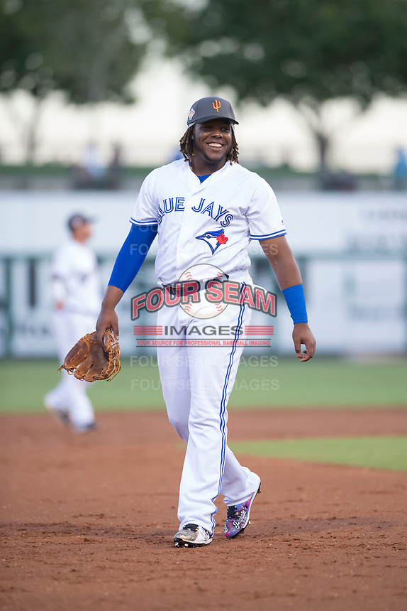 AFL West third baseman Vladimir Guerrero Jr. (27), of the Surprise Saguaros and Toronto Blue Jays organization, jokes with players on the AFL East team during the Fall Stars game at Surprise Stadium on November 3, 2018 in Surprise, Arizona. The AFL West defeated the AFL East 7-6 . (Zachary Lucy/Four Seam Images)