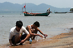 CAMBODIA  -  APRIL 3, 2005:  Two boys look for sea shells on the shore of Rabbit Island on April 3, 2005 in Cambodia.  Kep can be seen on the other side of the water.  (PHOTOGRAPH BY MICHAEL NAGLE)