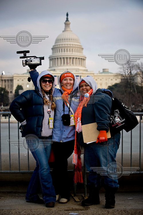 Students from Pitzer College in Claremont, California pose in front of the Capitol on the eve of the inauguration of Barack Obama as the 44th President of the United States. They carry a video camera to record the event for posterity.