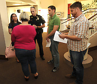 NWA Democrat-Gazette/ANDY SHUPE<br /> A Fayetteville Police officer (center) speaks Tuesday, Aug. 11, 2015, with Danielle Weatherby (from left), Laura Phillips, Kyle Smith and Nate Kennedy, all representatives from the For Fayetteville Campaign,  before escorting them off the property without incident during a rally in opposition of the city of Fayetteville's proposed Uniform Civil Rights Protection ordinance at University Baptist Church in Fayetteville. Protect Fayetteville organized the rally as a &ldquo;rally against religious persecution&quot; ahead of the Sept. 8 vote to approve the ordinance.
