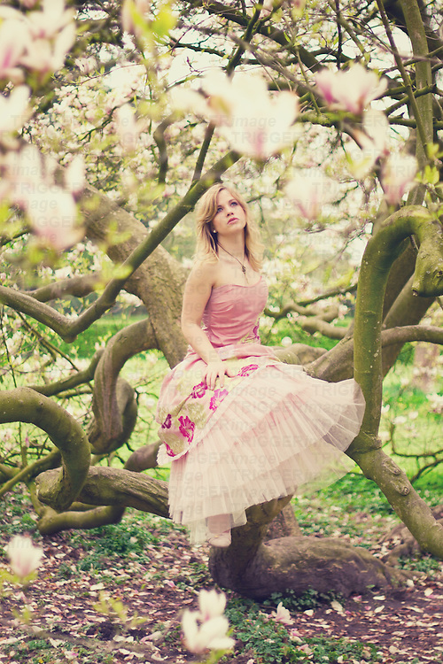A young blonde woman wearing a fancy pink dress in the sprintgime sitting at a magonlia tree