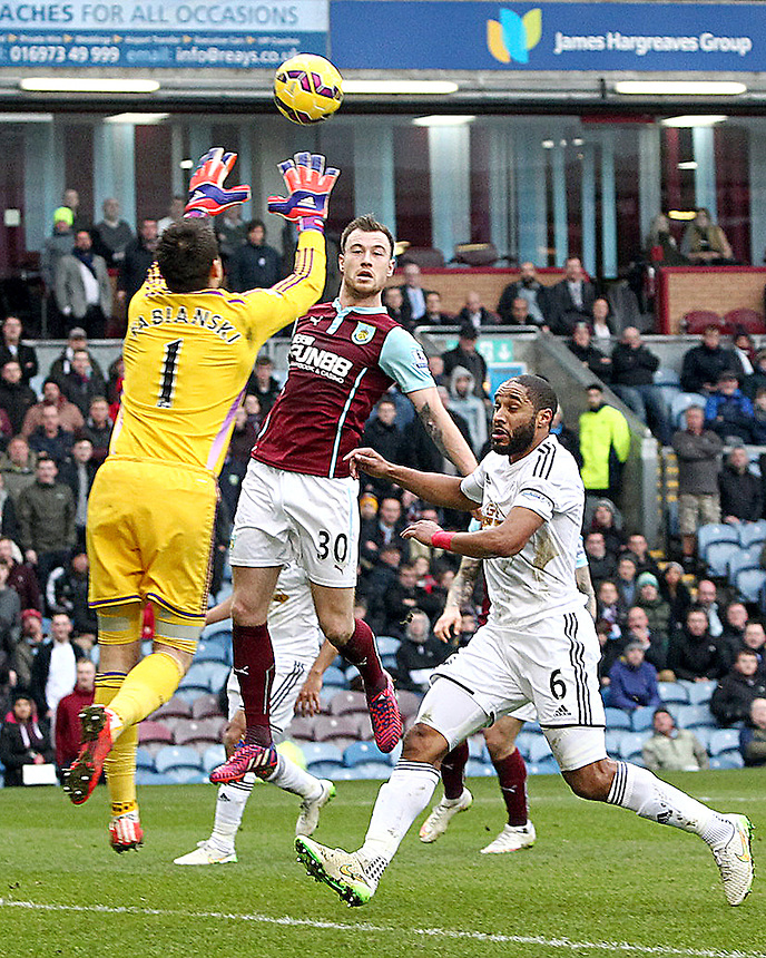 Swansea City's Lukasz Fabianski collects an aerial ball under pressure from Burnley's Ashley Barnes<br /> <br /> Photographer Rich Linley/CameraSport<br /> <br /> Football - Barclays Premiership - Burnley v Swansea City - Friday 27th February 2015 - Turf Moor - Burnley<br /> <br /> &copy; CameraSport - 43 Linden Ave. Countesthorpe. Leicester. England. LE8 5PG - Tel: +44 (0) 116 277 4147 - admin@camerasport.com - www.camerasport.com