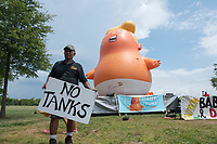 "Lucio Camacho holds a sign reading ""No Tanks"" in front of the ""Baby Trump"" blimp in Washington D.C., U.S. on July 4, 2019, to protest United States President Donald J. Trump's Salute to America speech.  The group believes the president's participation in 4th of July celebrations is politicizing a non-political holiday. Photo Credit: Stefani Reynolds/CNP/AdMedia"