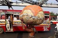 A man carries a large basket on his head across the Howrah bridge in central Kolkata.<br />