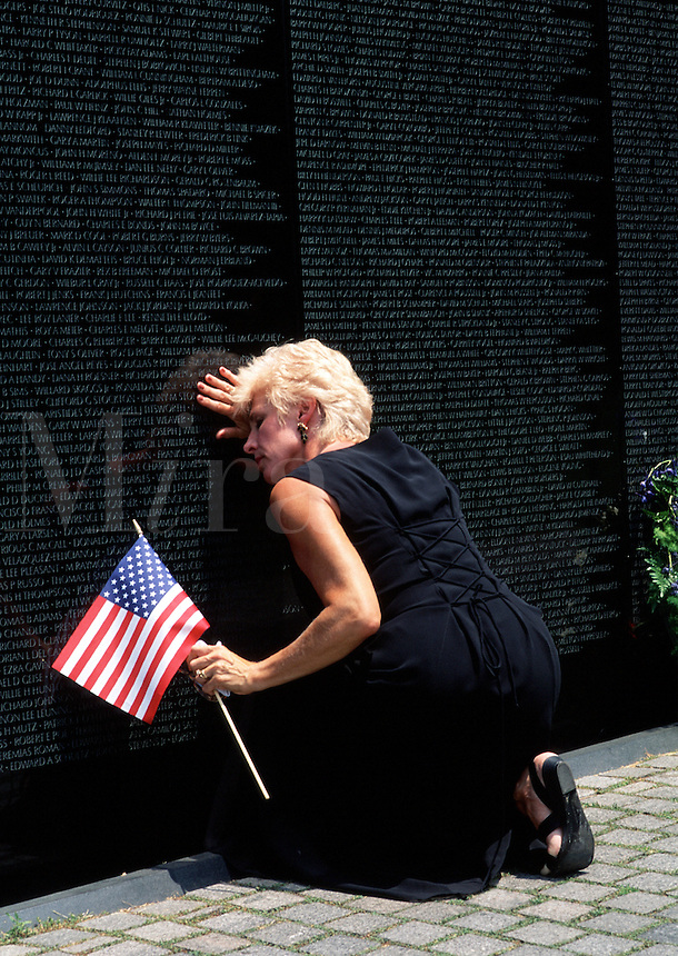 A grieving woman holds an American flag as she kneels to mourn her dead at the Vietnam War Memorial. Washington, DC.