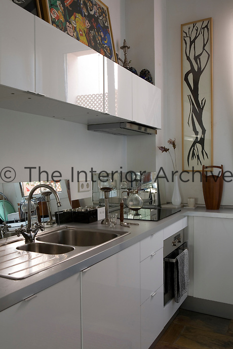 A modern white kitchen with a stainless steel sink and integral oven