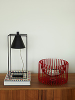 A vintage table lamp and a red plastic covered wire bowl stand on a wooden sideboard.