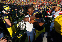 Ohio State Buckeyes cornerback Bradley Roby (1) embraces Michigan Wolverines tight end Devin Funchess (87) after the college football game between the Ohio State Buckeyes and the Michigan Wolverines at Michigan Stadium in Ann Arbor, Michigan Saturday afternoon, November 30, 2013. The Ohio State Buckeyes defeated the Michigan Wolverines 42 - 41. (The Columbus Dispatch / Eamon Queeney)