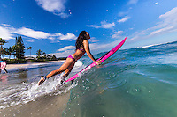 A local surfer girl jumps into the ocean for a surf session, Laniakea Beach, North Shore, O'ahu.