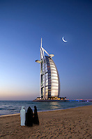 Family stands on the beach in front of the Burj al Arab Hotel, architects W. S. Atkins,  an icon of Dubai built in the shape of the sail of a dhow on an artificial island just off Jumeirah Beach. Evening.  Dubai. United Arab Emirates.