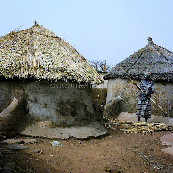 A woman fixing the roof of her hut.