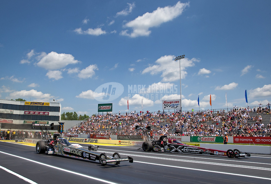 Jun. 2, 2013; Englishtown, NJ, USA: NHRA top fuel dragster driver Brittany Force (left) races alongside Spencer Massey during the Summer Nationals at Raceway Park. Mandatory Credit: Mark J. Rebilas-