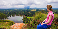 Panoramic photo at Sigiriya Rock. A tourist enjoying the panoramic view over the Sri Lanka landscape. This is a panoramic photo of a tourist enjoying the view over the Sri Lanka landscape from Sigiriya Rock Fortress, aka Lion Rock, a UNESCO World Heritage Site in Sri Lanka. Sigiriya Rock is easily the most popular tourist attraction in Sri Lanka, renowned for its 360 degree panoramic views of the surrounding Sri Lanka landscape.