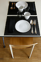 A detail of the dining table laid with simple white crockery and black place mats