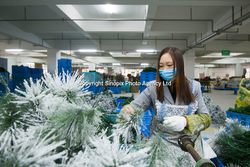 November 28, 2015, Yiwu China - A female worker makes Christmas trees inside Sinte An Christmas tree factory. The factory produces a variety of artificial trees for global export throughout the year.Photo by Dave Tacon / Sinopix