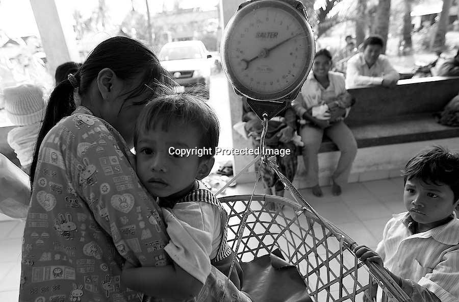 Health center Cambodia. Women are using a rattan basket to weigh their young children. Trapeng Andeuk, Takeo province, Cambodia-2009