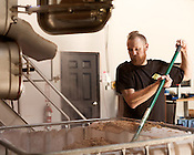 August 7, 2013. Hillsborough, North Carolina.<br />  Brewer Chris Shields empties the malt into a large container that will be given to local farmers for feeding cattle and other livestock.<br />  Mystery Brewing Co. is just one of several new breweries to open up in Orange County over the last year. With a taproom just up the road, Mystery has become increasingly popular as the craft beer market in North Carolina grows.