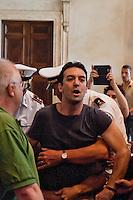 Roma, 11  Luglio 2012.Consiglio comunale in Campidoglio nell'aula Giulio Cesare per  la discussione sulla  cessione del 21% della controllata Acea, l'azienda che si occupa di acqua e servizi.Un attivista dei comitati «Acqua pubblica» contesta  il Presidente del Consiglio Comunale, Marco Pomarici e viene bloccato dalla Polizia Municipale