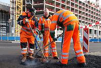 Wegwerkerkers repareren de gaten in het wegdek