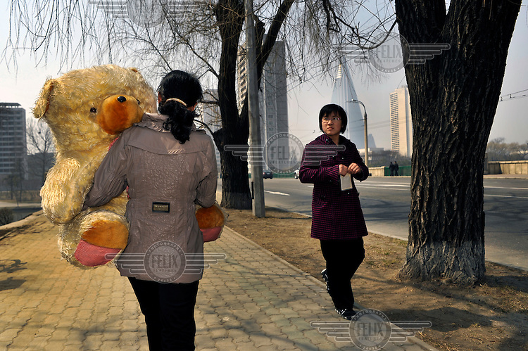 A woman carries a giant teddy bear along a roadside.