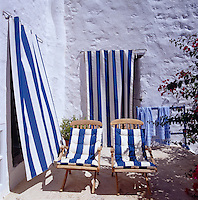 Blue and white striped canvas door curtains and matching cushions on a pair of sun-loungers make a bold statement on the terrace