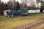Travellers site of old vans and caravans in woodland, Sutton heath, Suffolk, England