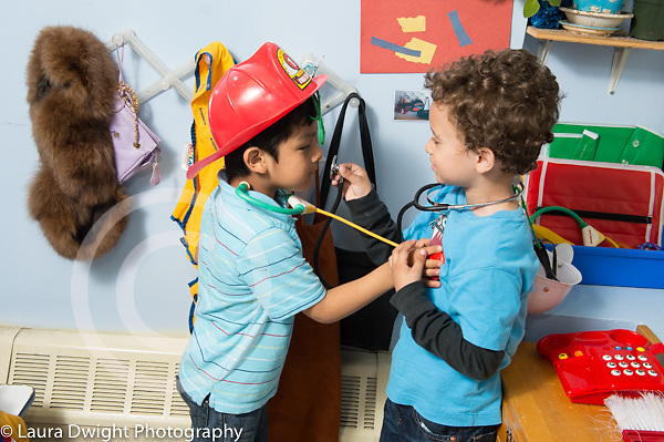 Education preschool 3 year olds pretend play dressup two boys laughing and interacting using toy stethoscopes