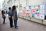 Voters look a board displaying posters of local candidates for Japan's upper house election at a polling station in Tokyo, Japan on July 10, 2016. (Photo by AFLO)