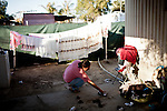 Margarita Avila picks up spilled laundry at her home in the Rancho Garcia trailer park in Thermal, Calif., March 9, 2012.